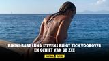 Bikini-babe Luna Stevens buigt zich voorover en geniet van de zee